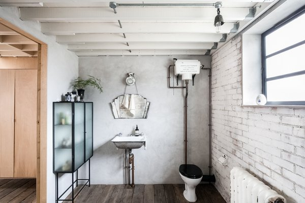 Bath Room, Dark Hardwood Floor, Two Piece Toilet, Wall Mount Sink, Wall Lighting, and Ceiling Lighting Decorated with distinctive vintage and contemporary pieces, this bathroom has loads of individuality.  Photo 9 of 11 in Snap Up This Converted  Warehouse in London For $2.1M