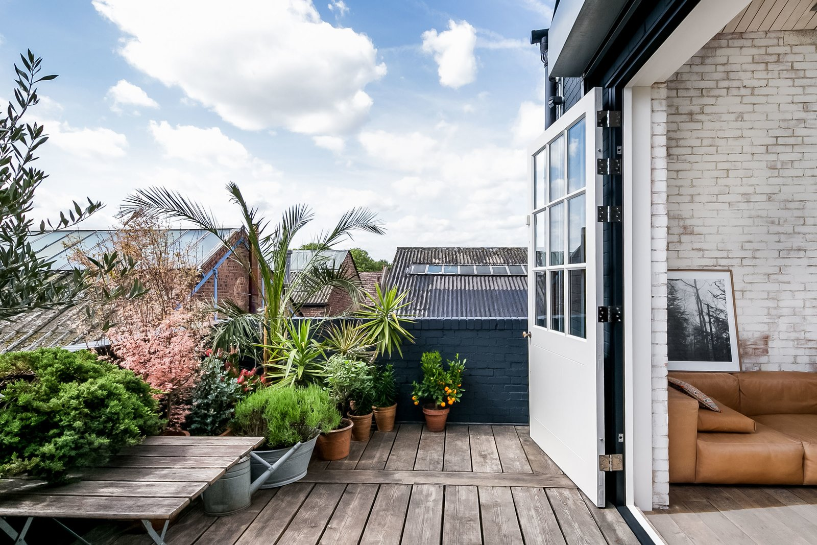 Outdoor, Shrubs, Wood Patio, Porch, Deck, Flowers, Rooftop, and Small Patio, Porch, Deck The generous decked terrace gets plenty of sun, making it a great spot for plants that prefer warmer climes.  Photo 6 of 11 in Snap Up This Converted  Warehouse in London For $2.1M