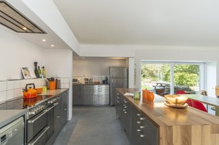 The recently renovated kitchen is now spilt into two sections and features industrial stylings, giving it the look of a commercial kitchen. The deep orange accessories, along with the wooden worktop on the island, brightens the overall gray-toned space.
