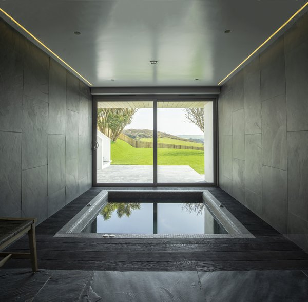 With dark gray tiles that mimic stone and atmospheric lighting, this cave-like space has a soothing feel while evoking elemental landscapes. The picture window provides scenic views of the garden, grassland, and the hills beyond while you relax in the spa bath.
