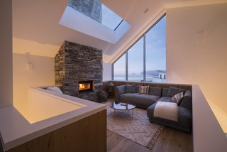 The chimney is clad in stone, with a fireplace on each floor, and can be seen through the large skylight in this living space.