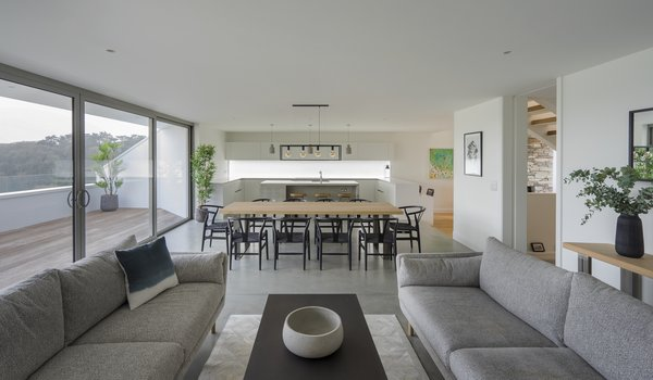 The living space in the open-plan kitchen/dining/living spaces flows out onto the south-facing terrace. The soft gray color scheme works with Cornwall's cool light and large skies.