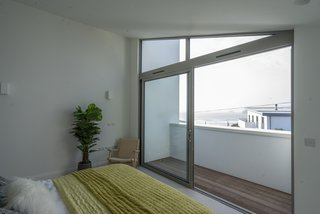 You can hear and see the ocean from this bedroom, which features a covered terrace and full-length glazed sliding doors and a window above.