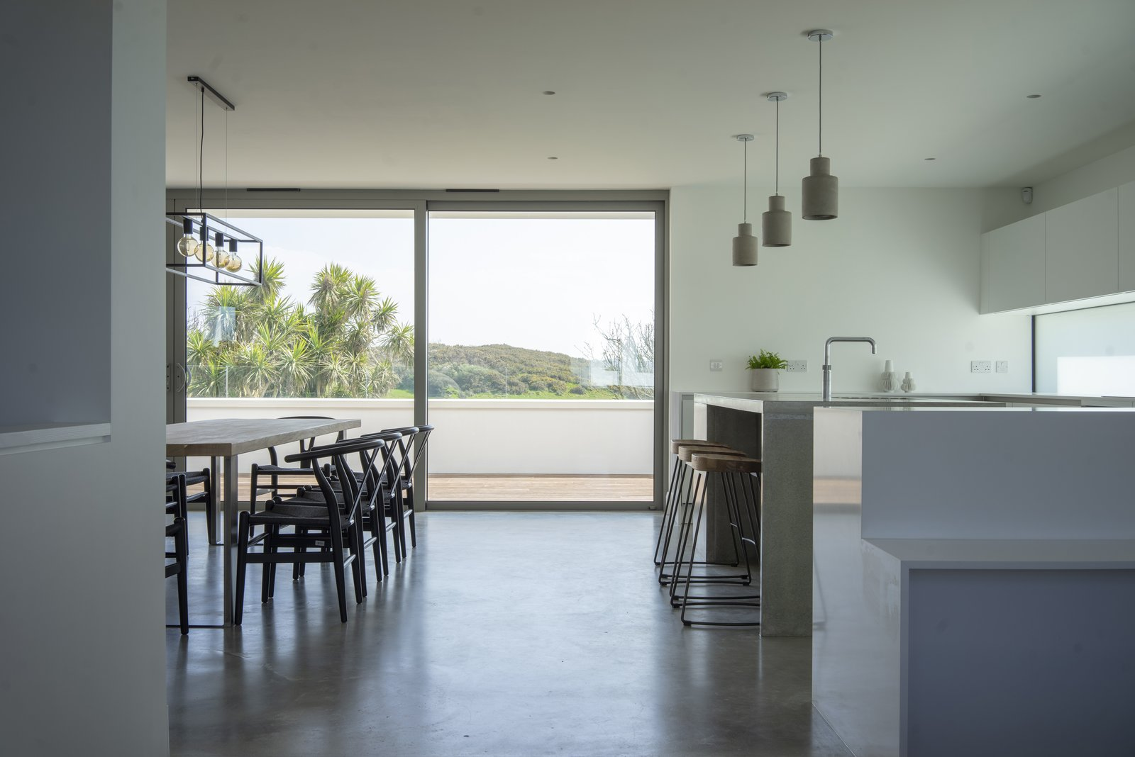 Dining, Bar, Concrete, Recessed, Stools, Table, Chair, and Pendant A mix of Scandinavian and industrial furnishing add interest to the streamlined kitchen.  Best Kitchen Drop In Vinyl Photos from A UK Home With Panoramic Ocean Vistas Asks $3.5M