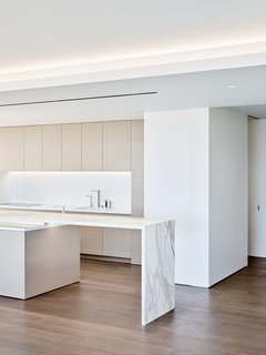 The crisp white kitchen features appliances built into the cabinetry and marble countertops.