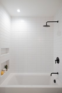 Each bathroom features matte black hardware and oversized Phylrich rain shower heads.