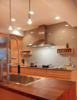 Modern home with Kitchen, Glass Tile Backsplashe, Range Hood, Cooktops, Wood Counter, Pendant Lighting, Stone Counter, Recessed Lighting, Undermount Sink, Refrigerator, and Wood Cabinet. Kitchen island and glass wall backsplash at cooktop. Photo 3 of Modern Remodel in Traditional Home
