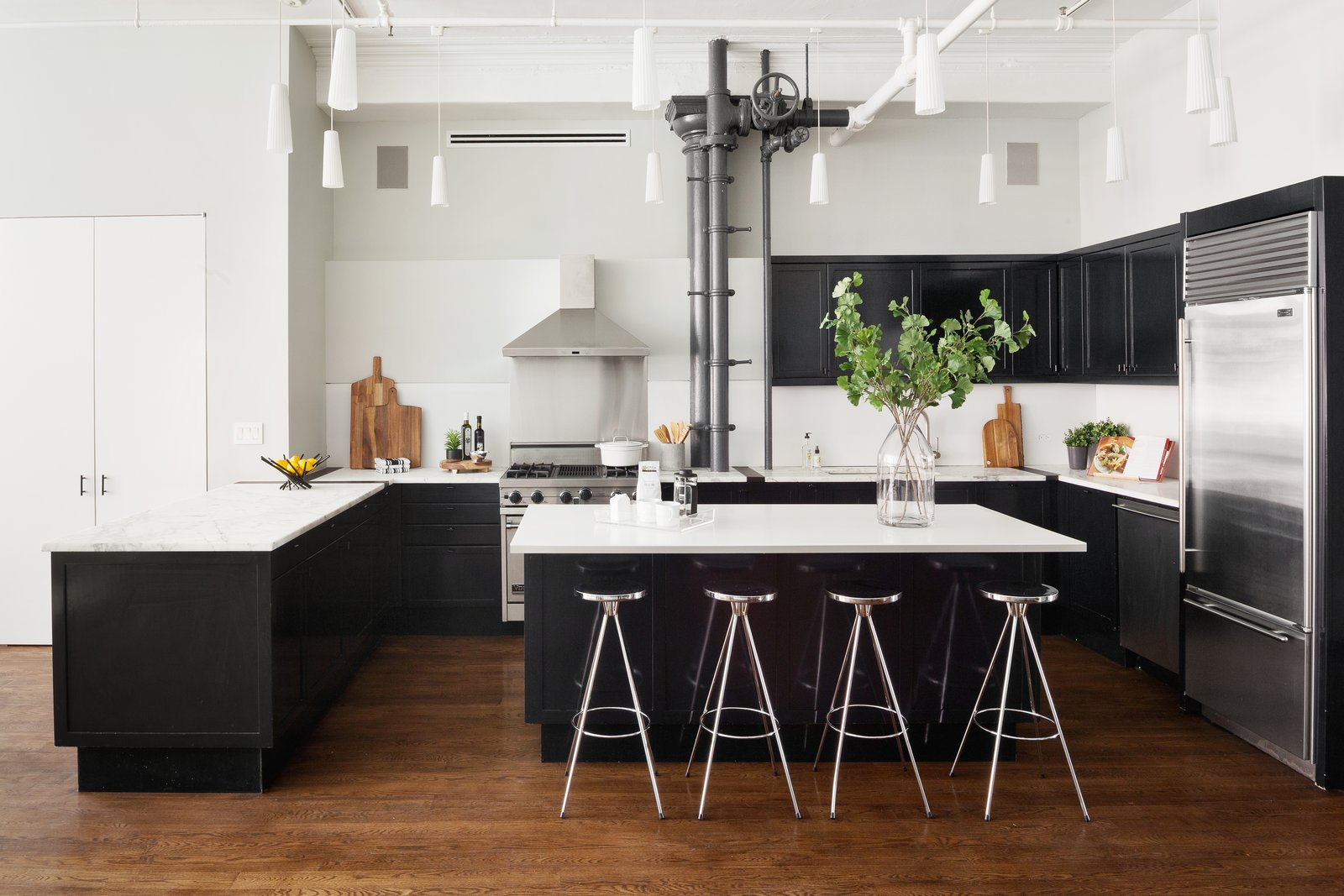 Kitchen, Medium Hardwood, Refrigerator, Range Hood, Wine Cooler, Dishwasher, Wood, Drop In, Range, and Track The chef's kitchen has an eat-in counter, Miele appliances, and a wine cooler.  Best Kitchen Track Medium Hardwood Photos from Classic Soho Loft