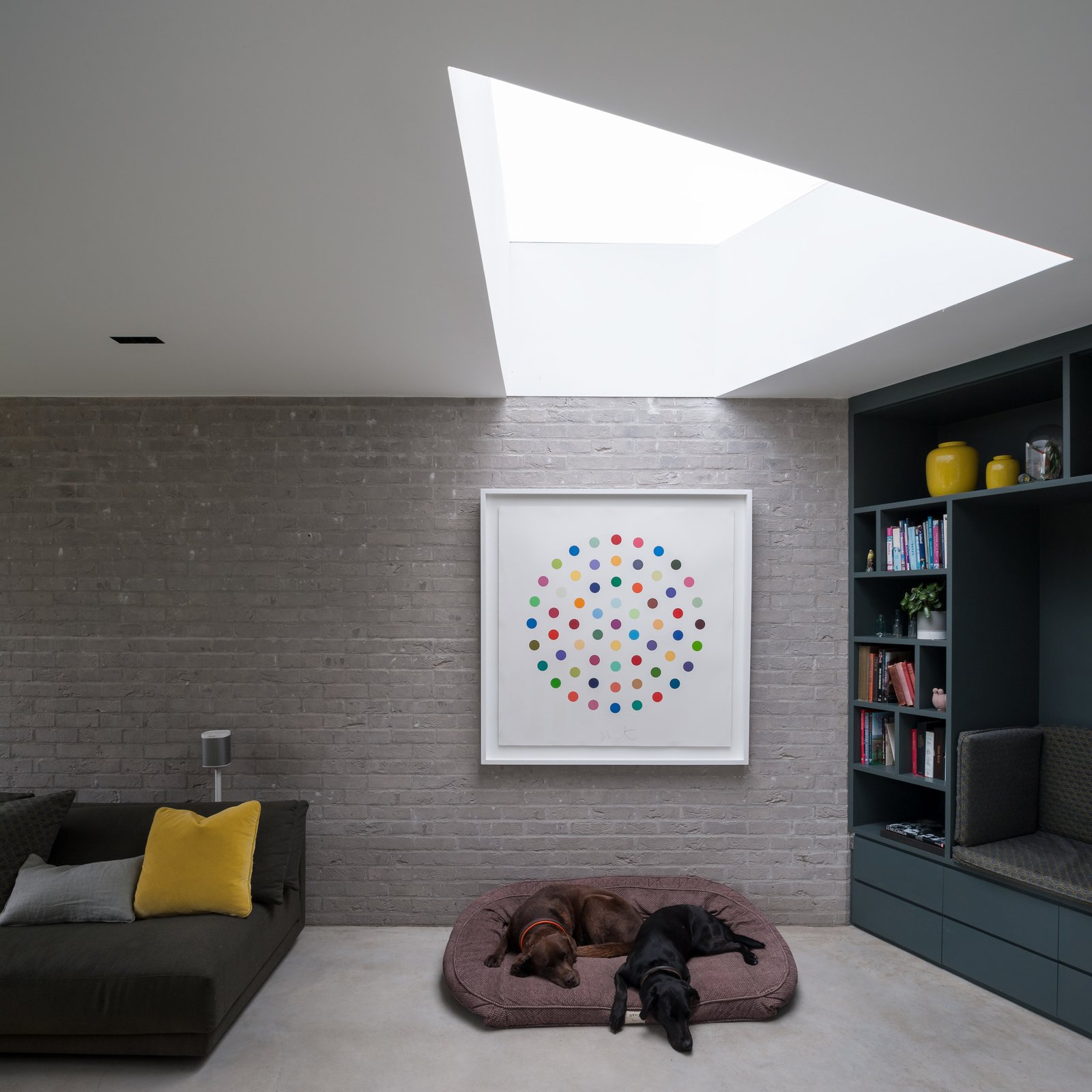Living Room, Bookcase, and Concrete Floor A wedge-shaped skylight allows natural light to suffuse the interiors. The architects preserved a palette of dark, natural materials on the ground floor.  Best Photos from Oatlands