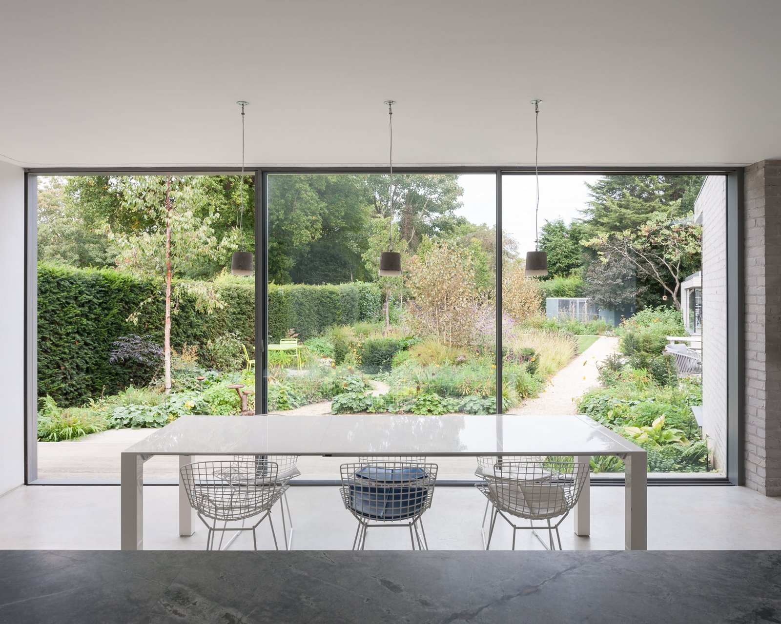 Dining Room, Concrete Floor, Pendant Lighting, and Table Generous glazing mimics the experience of dining outdoors.  Best Photos from Oatlands