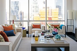 A duet of orange leather table lamps from Armani/Casa add a dash of orange that is echoed throughout the living room.