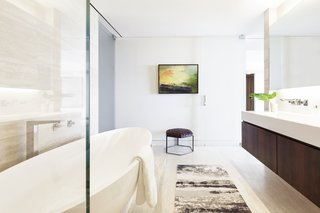 A clean master bathroom palette was embellished with a stylish area rug.