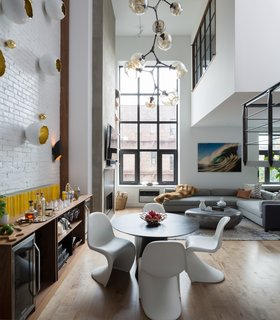 The couple loves to entertain, so it was important that the downstairs living area have a good flow between the kitchen, dining, and living areas. A dramatic chandelier from Lindsey Adelman hangs from the double-height ceiling, punctuating the space.