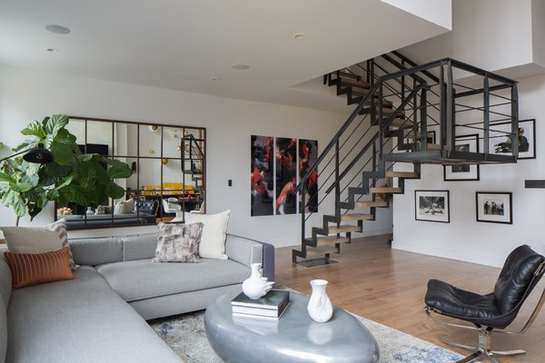 We also sourced two Panton Chairs, from Design Within Reach. An area rug from Tom Dixon's collection for The Rug Company adds a sophisticated, urban edge to the design. The staircase, which is prominently positioned in the center of the living area, featured iron railings, so we created continuity by refinishing the fireplace in iron and cement.