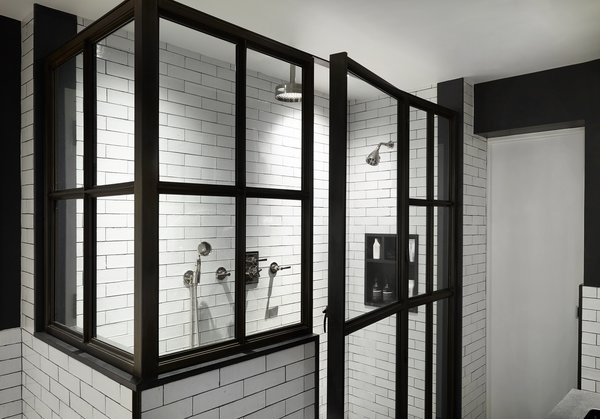 In the industrial-feeling master bath, we replaced the existing tub with a larger, iron-and-glass shower, which features handmade white subway tiles. Brass mirrors hang over the new double vanity, which includes storage space underneath.