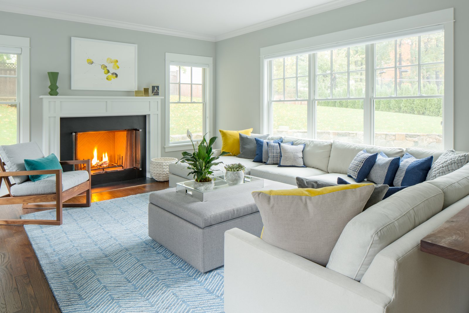 Living Room, Ottomans, Sofa, Chair, Standard Layout Fireplace, and Medium Hardwood Floor Colorful accent pillows and decorative geometric objects were added throughout the home, to further distinguish each room, and to offset the tasteful, neutral palette.   Contemporary Westchester Home