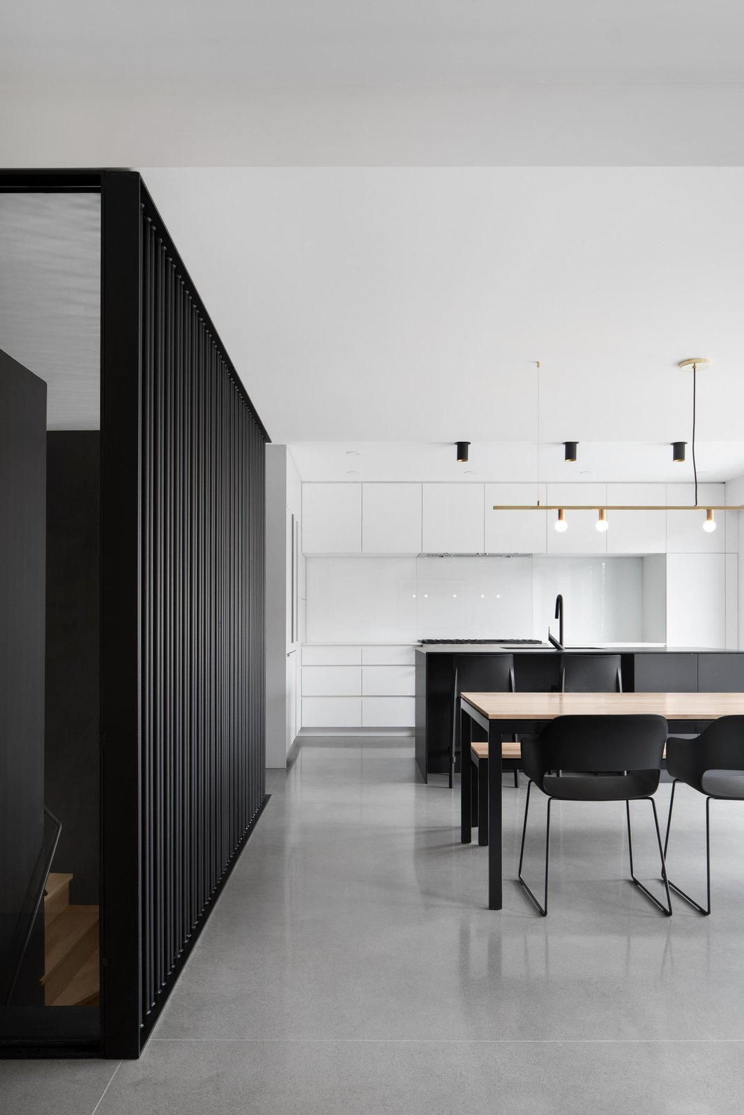 """Kitchen, Ceiling Lighting, Concrete Floor, and White Cabinet """"Reinforcing the degree of abstraction of the project, the choice of the minimalist furniture and lamps echoes the palette of textures composed of concrete, wood, and steel,"""" add the architects.  Best Photos from Bessborough Residence"""