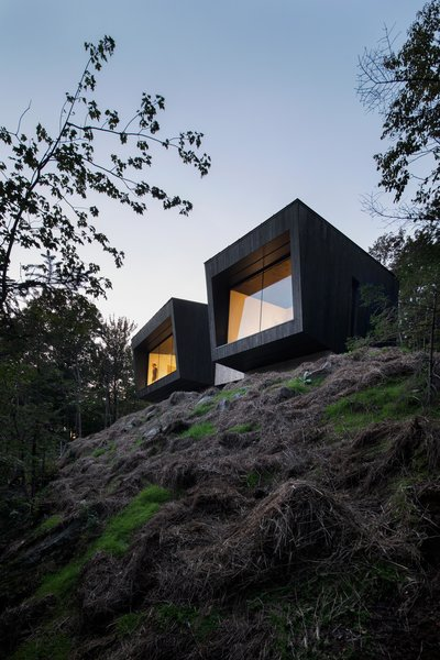 """""""At night, the chalet is transformed. When it is dark, the mirror effect of the reflection of the interior space in the windows completely changes the cabin's relationship to its site and makes it appear larger,"""" adds Rasselet."""