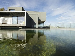 The design of this unique structure was oriented toward the exterior panoramic view. Beyond the western façade is a natural swimming pond.