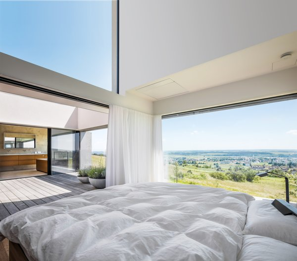 The master bedroom ceiling is 13 feet high and tilted to 29 degrees. When opened, the homeowners are able to sleep in the open air. Their request to the architect was that they be able to stargaze before falling asleep.