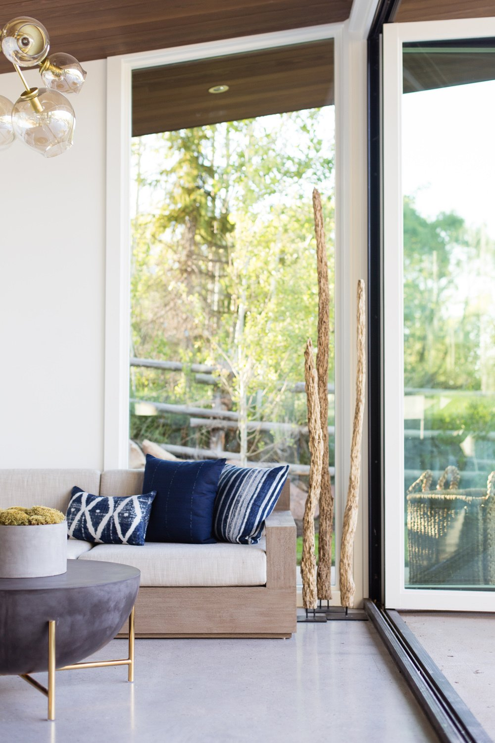 Living Room, Sofa, Ceiling Lighting, and Coffee Tables Brass accents brighten up the multifunctional space.  Photo 10 of 16 in This Can-Do Pool House Cleverly Goes From Private to Party Mode from Modern Mountain Pool House