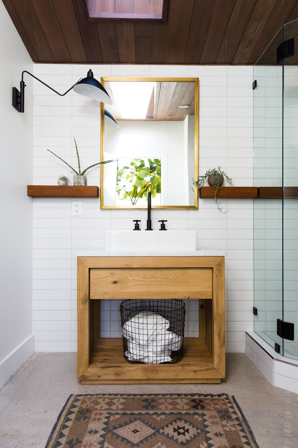 Bath Room, Vessel Sink, Wall Lighting, Rug Floor, Corner Shower, Marble Counter, and Concrete Floor Custom woodwork adds helpful shelving in the bathroom, while a long skylight draws in natural light.  Modern Mountain Pool House by Melissa Kelsey