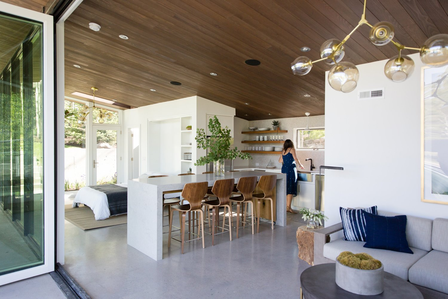 Dining Room, Recessed Lighting, Stools, Ceiling Lighting, Concrete Floor, and Table Clean, simple colors allow wood tones to glow, tying back to the outdoor environment.  Photo 8 of 16 in This Can-Do Pool House Cleverly Goes From Private to Party Mode from Modern Mountain Pool House