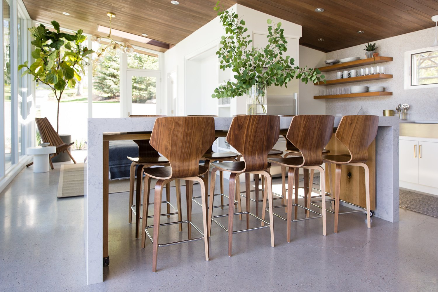 Dining Room, Table, Concrete Floor, Stools, Recessed Lighting, and Ceiling Lighting Resting on casters, a white oak island nestles under the quartz island in kitchen.  Photo 11 of 16 in This Can-Do Pool House Cleverly Goes From Private to Party Mode from Modern Mountain Pool House