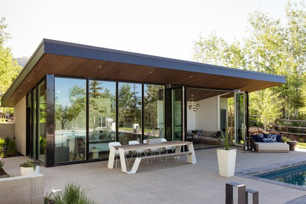 The bi-fold glass wall opens up to, and celebrates, the pool house's natural setting.