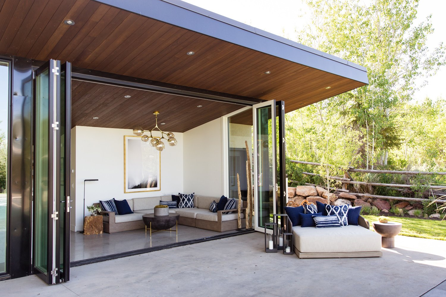 "Doors, Exterior, Metal, and Folding Door Type ""Everything is intended to blur the distinction between indoor and outdoor living,"" says Bellessa.   Photo 6 of 16 in This Can-Do Pool House Cleverly Goes From Private to Party Mode from Modern Mountain Pool House"