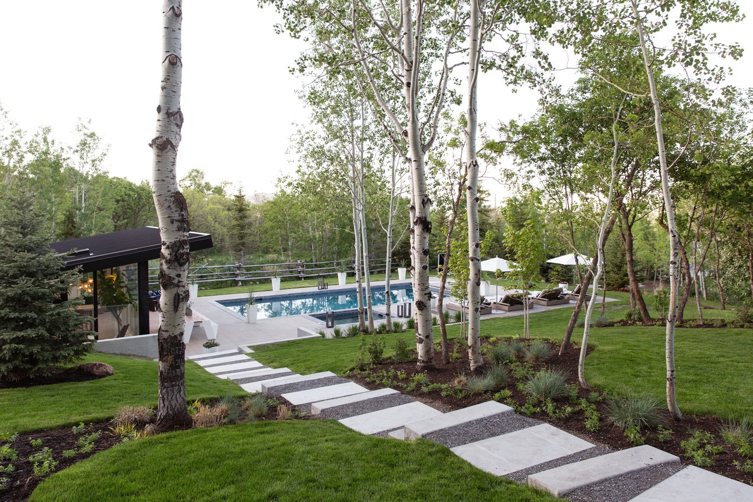 Outdoor, Walkways, Concrete Pools, Tubs, Shower, Woodland, Wood Fences, Wall, Trees, Shrubs, Swimming Pools, Tubs, Shower, Large Patio, Porch, Deck, Planters Patio, Porch, Deck, Horizontal Fences, Wall, Back Yard, Grass, and Concrete Patio, Porch, Deck The modern pool house emphasizes indoor/outdoor living. Landscaping was done by Eschenfelder Landscape Design.  Photo 2 of 16 in This Can-Do Pool House Cleverly Goes From Private to Party Mode from Modern Mountain Pool House