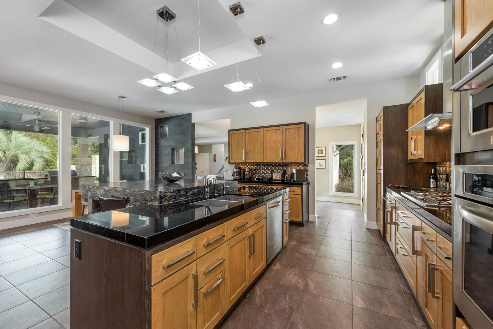 Kitchen, Porcelain Tile Floor, Wood Cabinet, Granite Counter, and Pendant Lighting Kitchen  The Carlson House