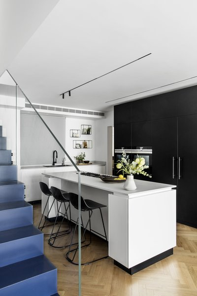 In an apartment renovation in Tel Aviv by Maya Sheinberger, a white and black kitchen comes together in a white island with black base and black bar stools by infiniti.