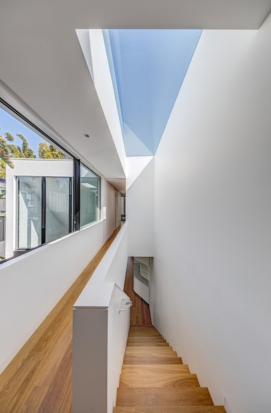A skylight runs the length of the stairs, allowing natural light to interact with interior surfaces.