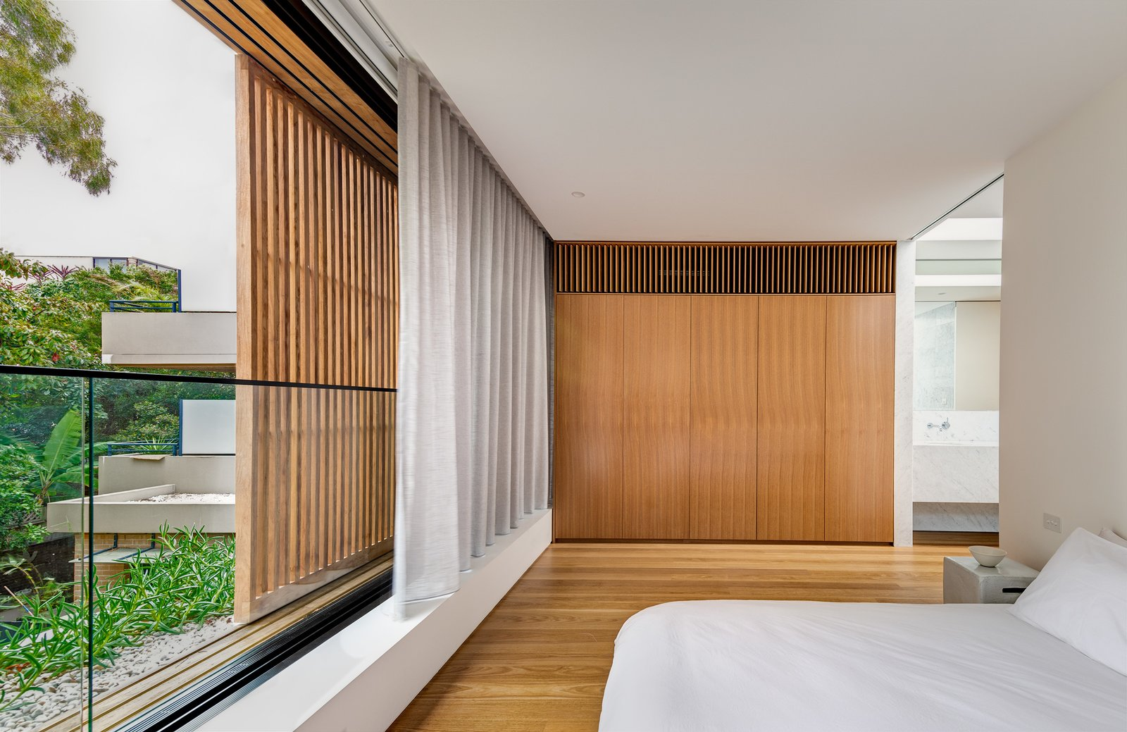 Bedroom, Ceiling Lighting, Bed, Medium Hardwood Floor, and Night Stands Master bedroom features sliding windows and privacy screens that span the width of the home.  Cloud House