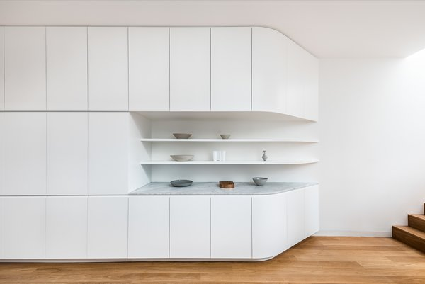 Custom cabinetry creates seamless kitchen and living storage solutions.
