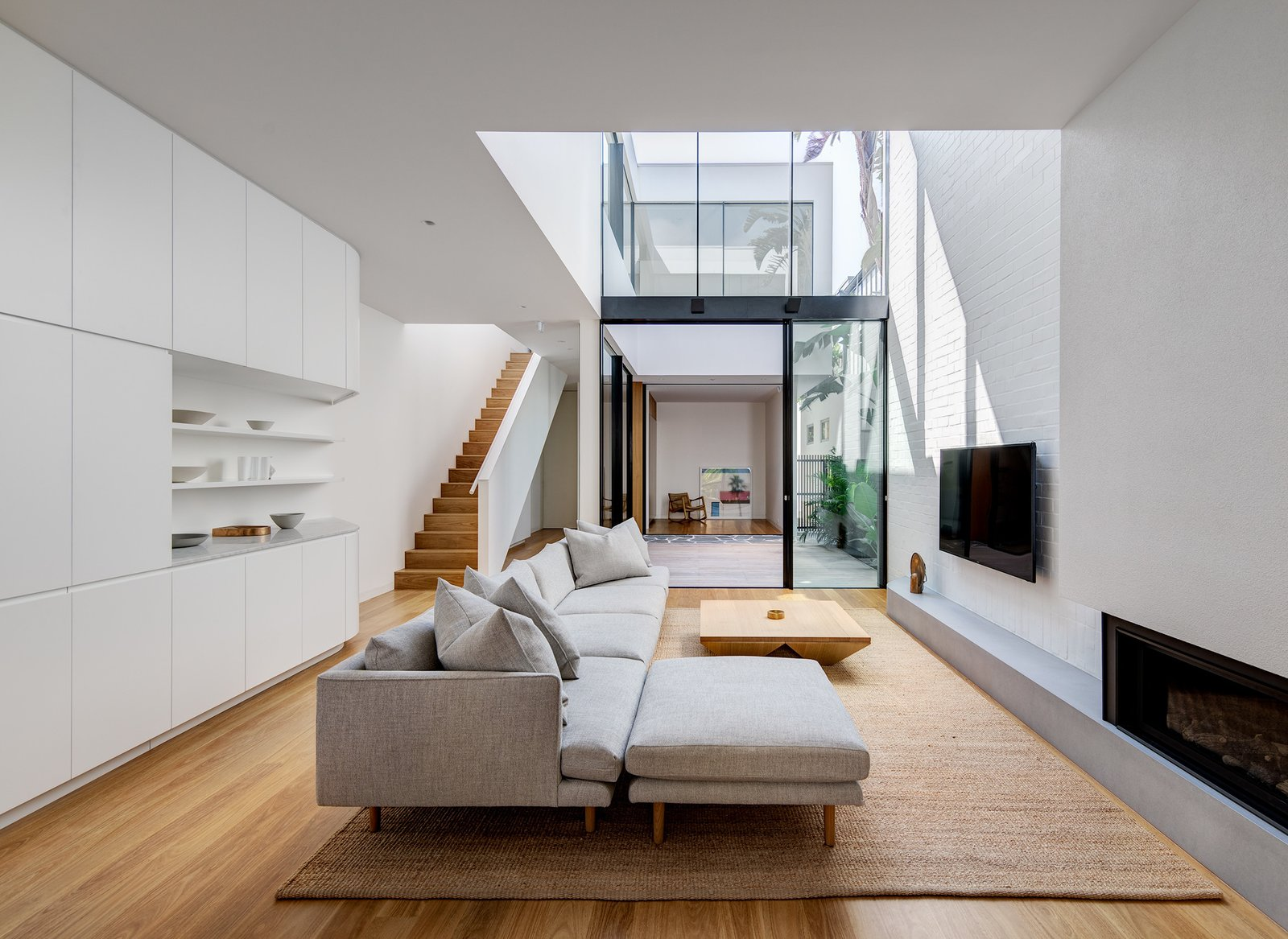 Living, Sofa, Corner, Coffee Tables, Ottomans, Medium Hardwood, Gas Burning, Bookcase, and Ceiling Double height living area opens onto the home's interconnecting courtyard and floods the living space with natural light.  Best Living Gas Burning Photos from Cloud House