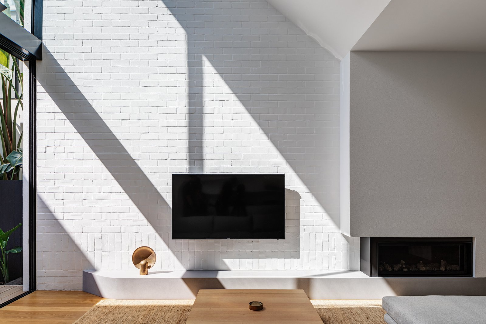 Living, Sofa, Ottomans, Medium Hardwood, Coffee Tables, Floor, Corner, Gas Burning, Ceiling, and Console Tables Double height living space opens to the North. The use of reclaimed bricks adds textural diversity.  Best Living Floor Gas Burning Photos from Cloud House