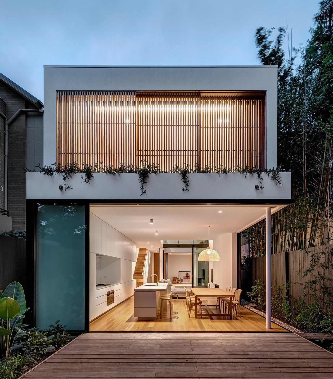 Outdoor, Back Yard, Wood Patio, Porch, Deck, Wood Fences, Wall, and Shrubs Designed by Sydney-based practice Akin Atelier, this Bondi Beach abode is comprised of two volumes connected by a central courtyard that draws in natural light. The orientation of the 2,010-square-foot home allows for a playful rhythm of light, shadow, and air that gives it its atmospheric name, Cloud House.  Photo 14 of 21 in Dwell's Top 10 Home Tours of 2019 from Cloud House