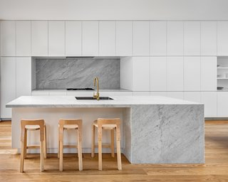 Kitchen with Carrara marble island and splash back. Custom cabinetry provides seamless storage options.