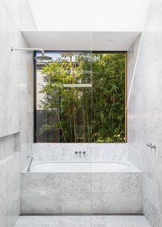 Bathroom features Carrara Marble flooring and walls. Window slides open on to garden foliage.