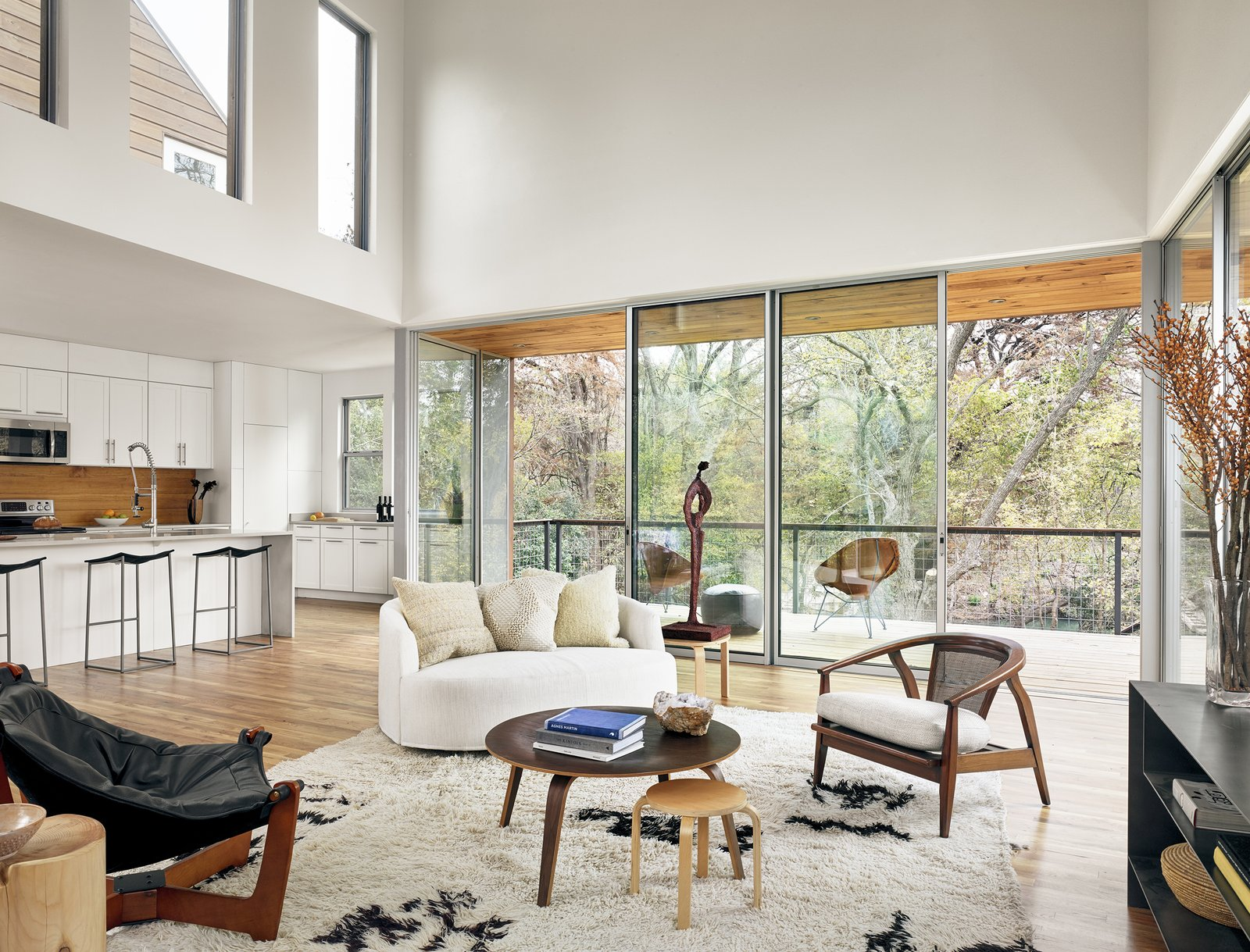 Living Room, Medium Hardwood Floor, Coffee Tables, Sofa, Stools, Rug Floor, Chair, Ceiling Lighting, Recessed Lighting, and Bar View of living area, kitchen, and outdoor porch by Low Design Office  Guadalupe River House