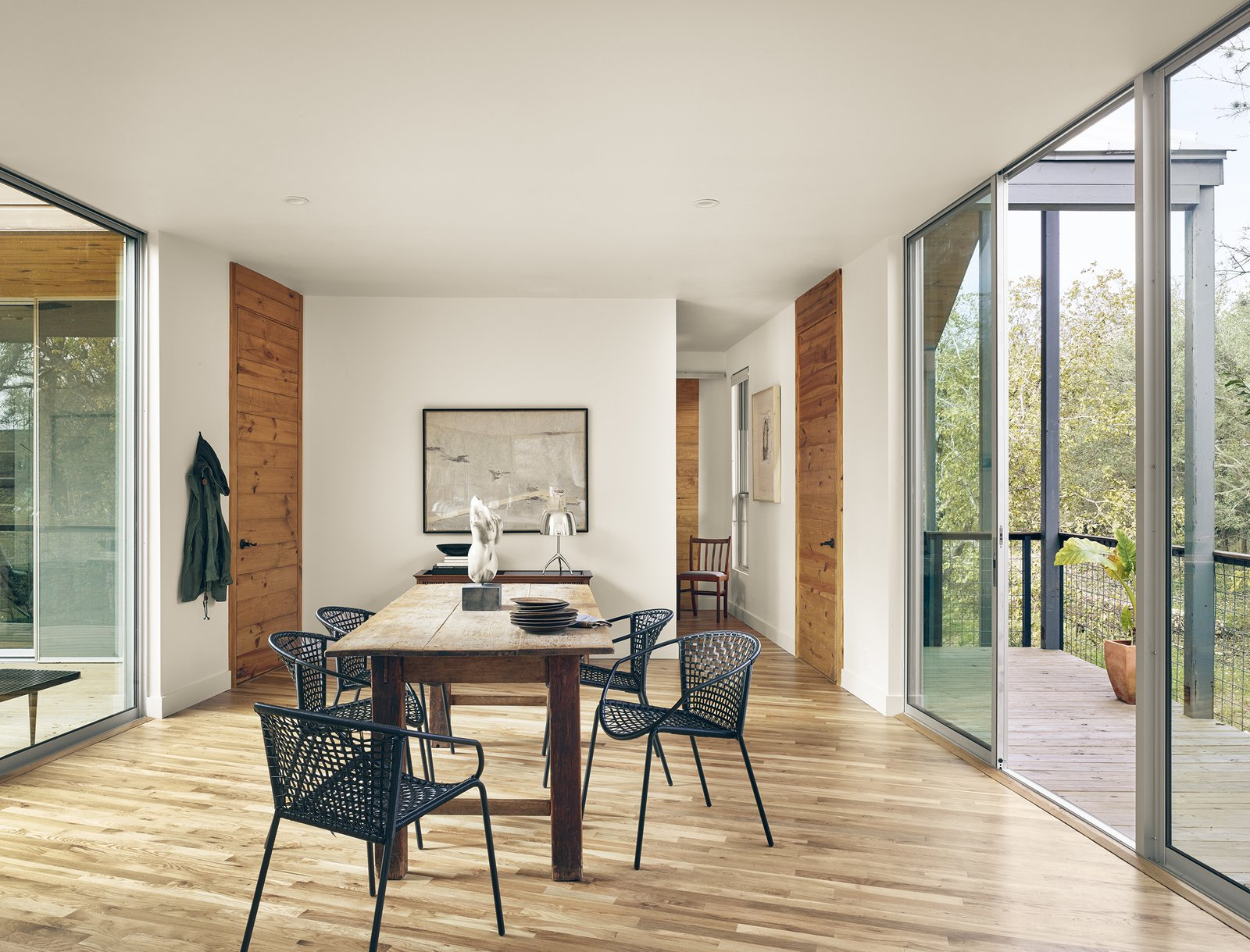 Dining Room, Medium Hardwood Floor, Table, Recessed Lighting, Wall Lighting, Chair, Ceiling Lighting, and Storage View of dining area and outdoor porch in the trees by Low Design Office  Guadalupe River House
