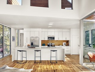 View of kitchen, outdoor porch, and roof deck above by Low Design Office