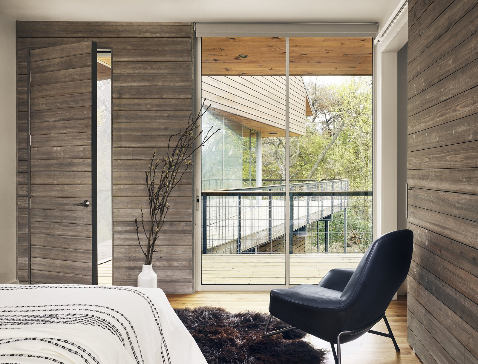 Bedroom, Recessed Lighting, Medium Hardwood Floor, Rug Floor, Bed, Ceiling Lighting, Wall Lighting, and Chair View of bedroom and outdoor porch by Low Design Office  Guadalupe River House