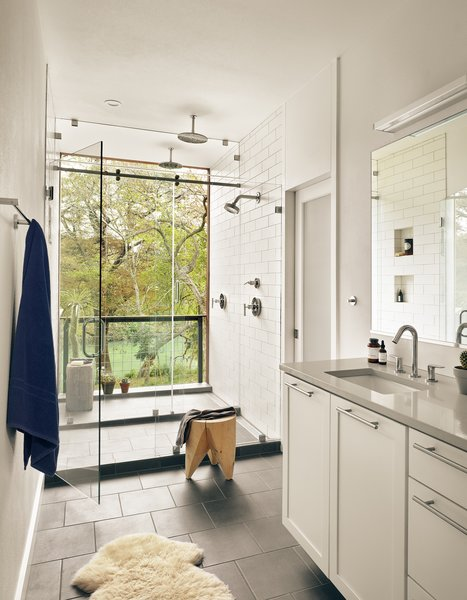 View of outdoor shower and Guadalupe River from master bathroom by Low Design Office