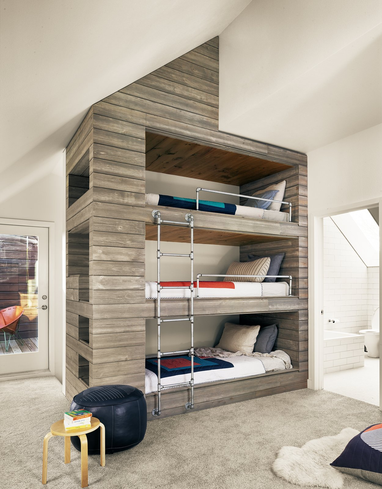 Kids Room, Bunks, Playroom Room Type, Family Room Room Type, Chair, Shelves, Storage, Bedroom Room Type, Bed, Rug Floor, Carpet Floor, Neutral Gender, Teen Age, Pre-Teen Age, and Toddler Age View of triple bunk bed and outdoor roof deck by Low Design Office  Guadalupe River House