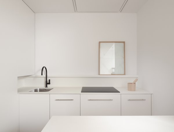 White laminate cabinets are the perfect solution to keep costs down for the small, open kitchen in this Madrid apartment.
