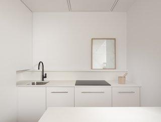 白色的层压板橱柜是保持成本低的小型开放式厨房在这个马德里公寓的完美解决方案。