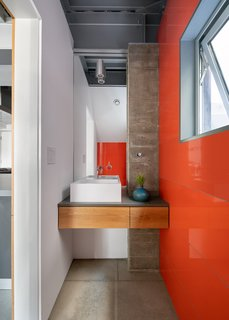 bathroom with concrete column and bold orange tile